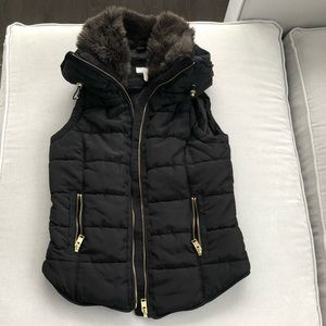 Puffy black vest with faux fur collar.